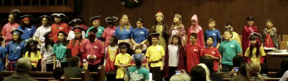 Assembly of special needs children singing on stage in costume
